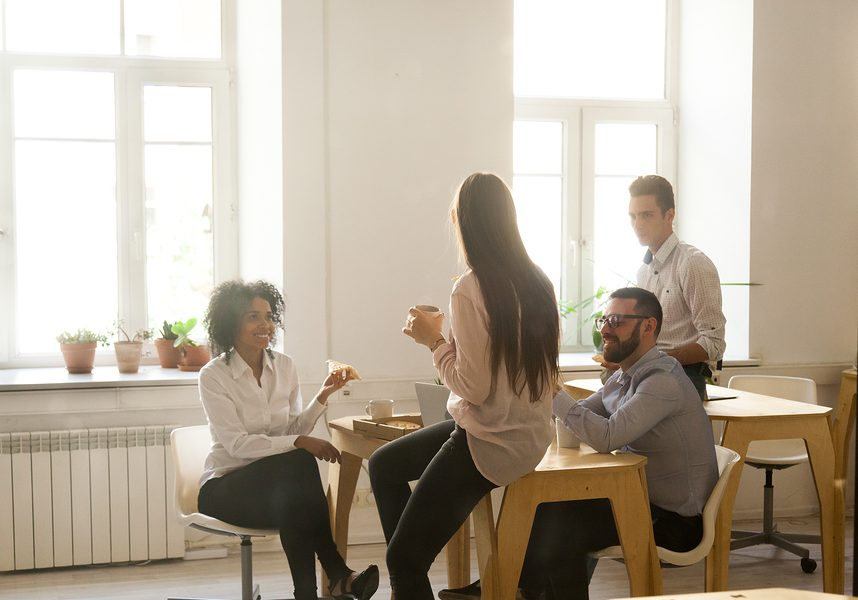 Smiling multiracial colleagues talking eating pizza at lunch in office room, diverse team people enjoy meal at coffee break chatting together, food delivery or good friendly relations at work concept